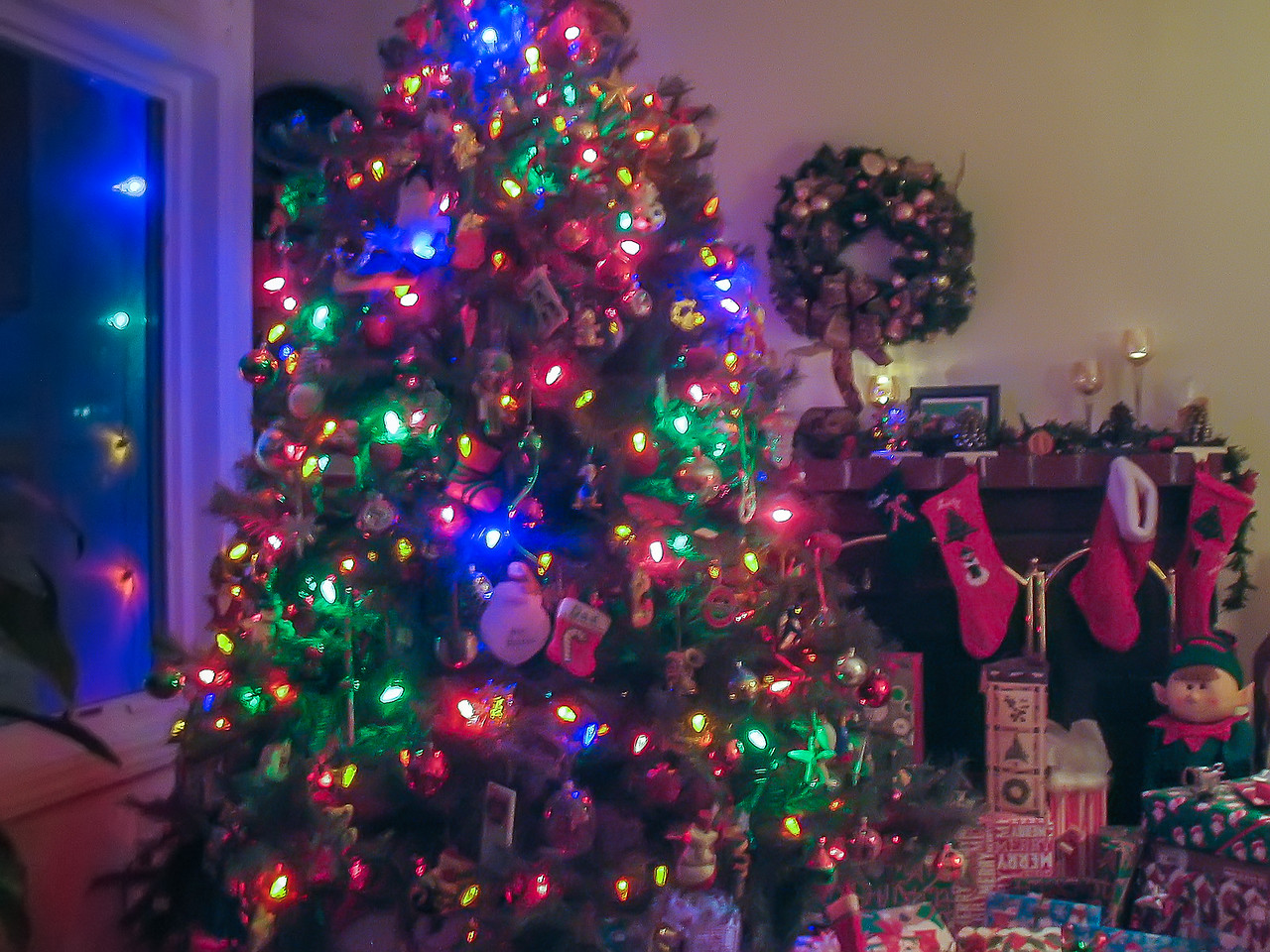 Christmas tree aglow with lights and surrounded by presents and stocking and decorations