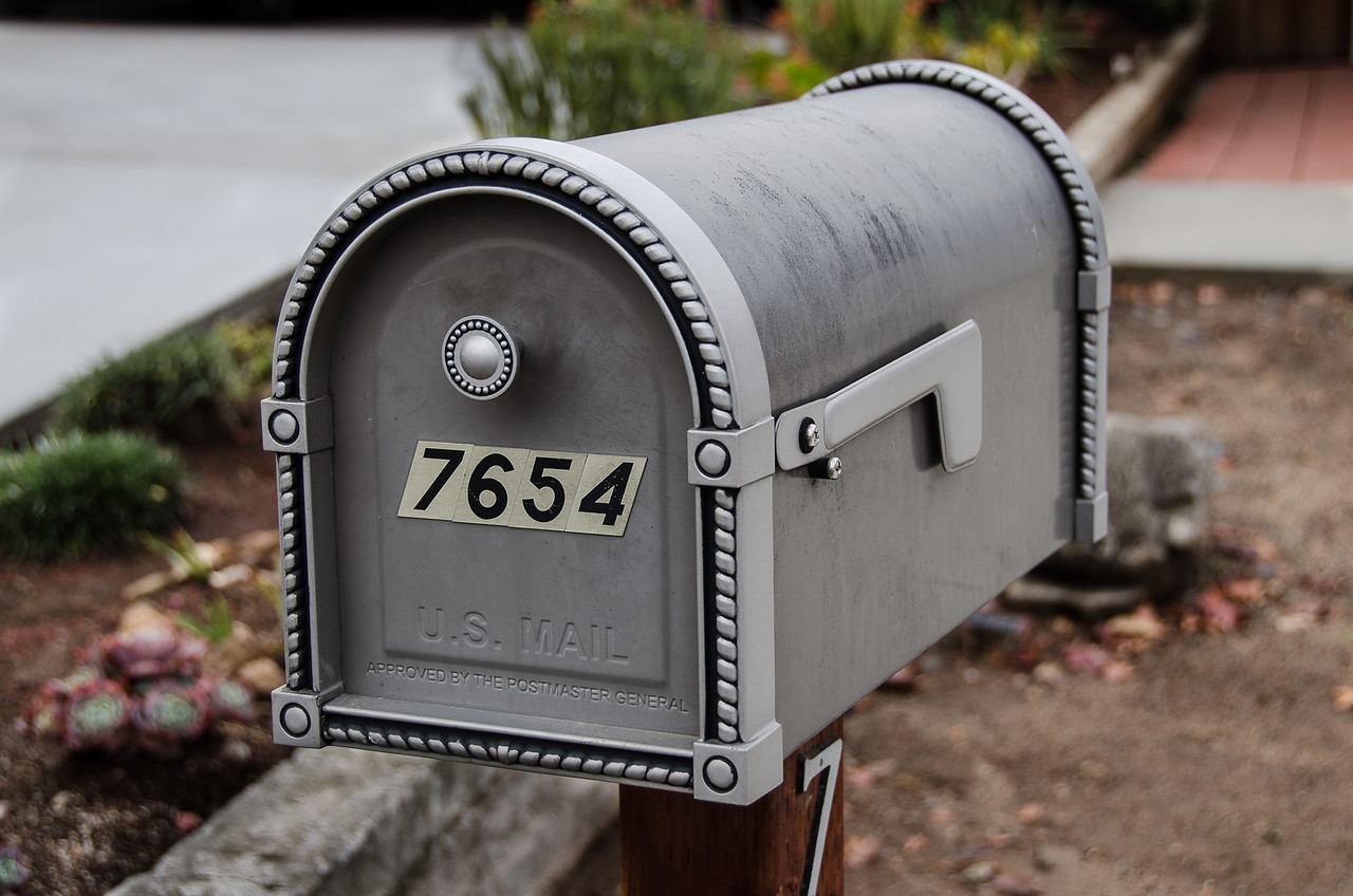 Simple pewter colored mailbox decorated with rope-like trim and a button handle