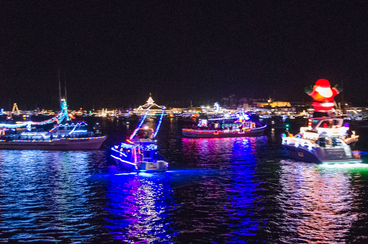 Brightly decorated boats chug about the harbor as part of the Christmas Boat Parade